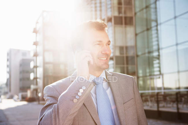 Mature businessman talking on cellphone in city — Stock Photo