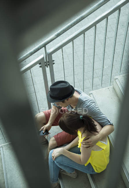 Vista de alto ângulo do jovem casal sentado na escada — Fotografia de Stock