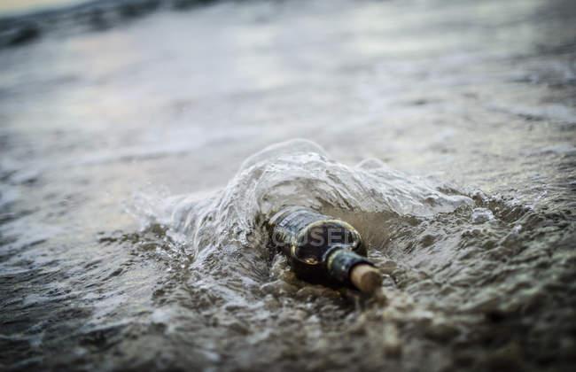 Wine bottle on beach shore in water — Stock Photo