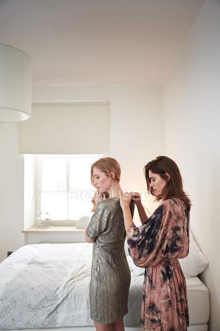 Due giovani donne si prepara in abiti zippare camera da ...