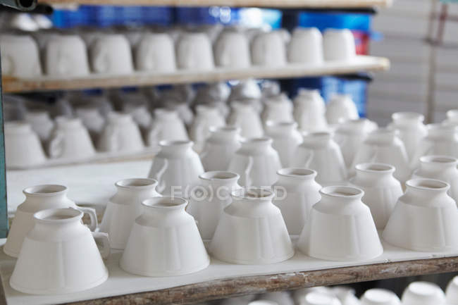 White teacups on table in pottery factory — Stock Photo