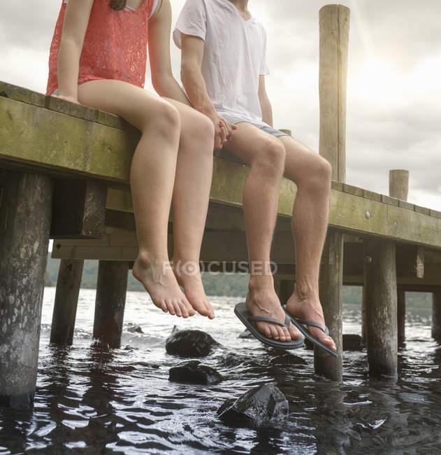 Mãos novas da terra arrendada dos pares junto e assento na borda do molhe sobre o lago, cortado — Fotografia de Stock