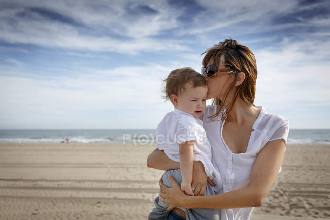 Mid adult woman kissing toddler daughter on beach, Castelldefels, Catalonia, Spain — Stock Photo