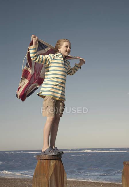 Хлопчик стоїть на стовпа проведення Юніон Джек прапор, Southwold, Саффолк, Великобританія — стокове фото