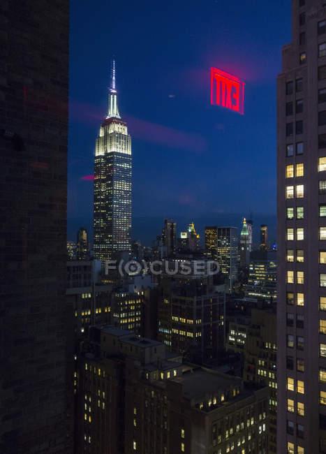 Blick durch Fenster des Empire State Building beleuchtet in der Nacht, New York, USA — Stockfoto
