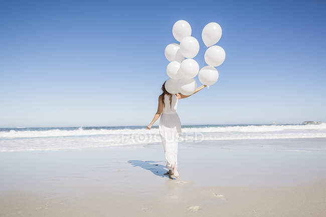 Full length rear view of woman on beach wearing white dress holding balloons — Stock Photo
