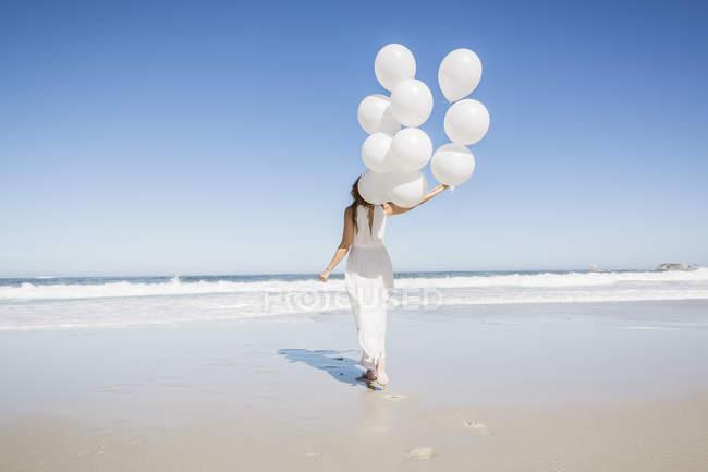 Повна довжина заднього виду жінці на пляжі білого плаття тримає повітряні кульки — стокове фото