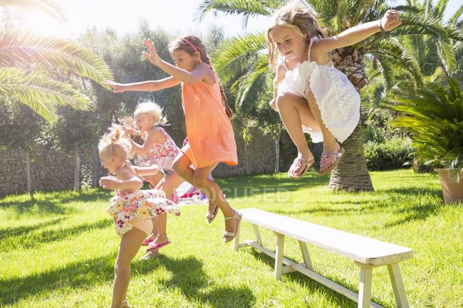 Five energetic girls jumping from garden bench — Stock Photo