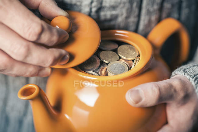 Мужские руки, держа чайник полный монет — стоковое фото