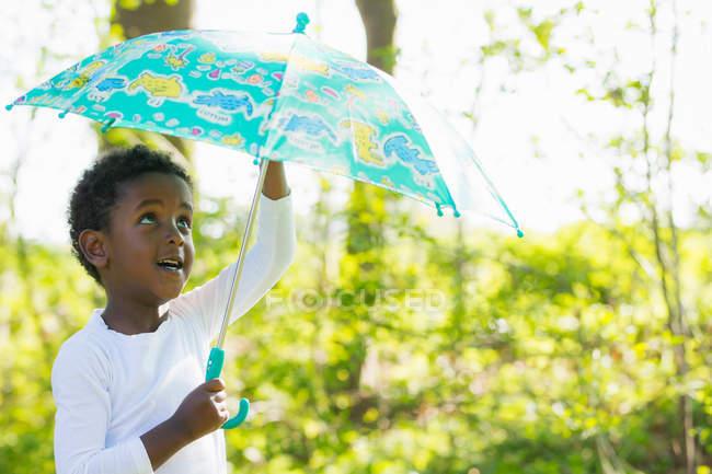 Niño llevando paraguas en el bosque — Stock Photo