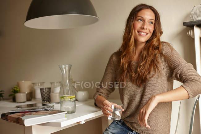 Улыбающаяся женщина пьет стакан воды — стоковое фото