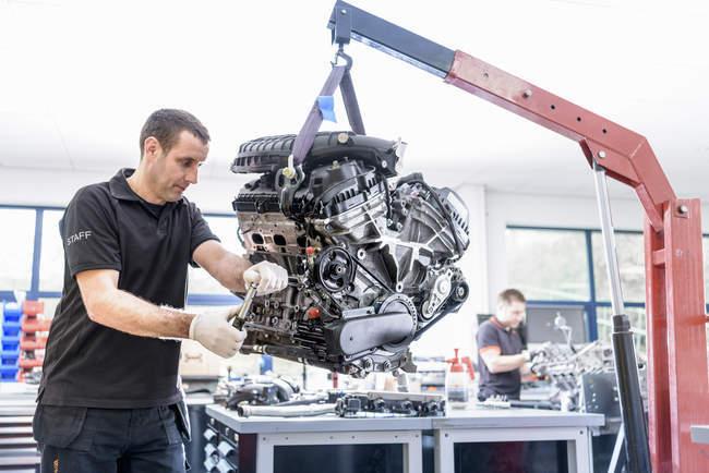 Ingenieure arbeiten an Motoren in Rennwagenfabrik — Stockfoto