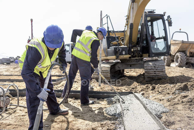 Apprentice builders laying concrete foundations on building site — Stock Photo