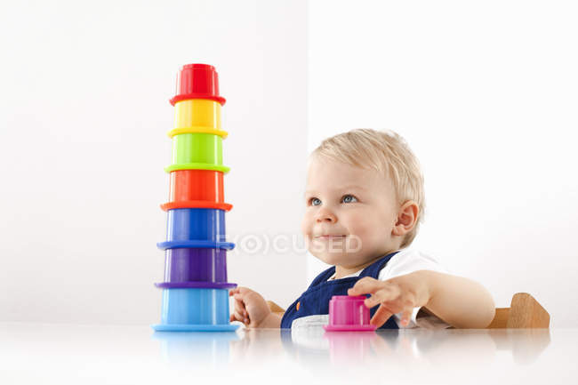 Little boy playing with stacking cups — Stock Photo