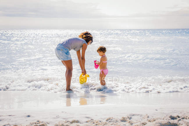 Mother and toddler daughter collecting water from sea, Tuscany, Italy — Stock Photo