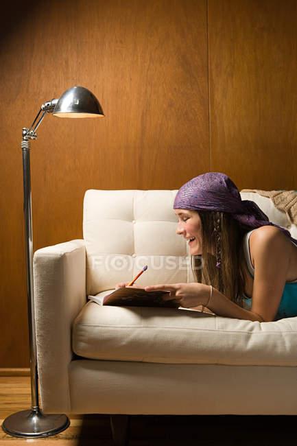 Ragazza adolescente che scrive nel diario sdraiato sul divano — Foto stock