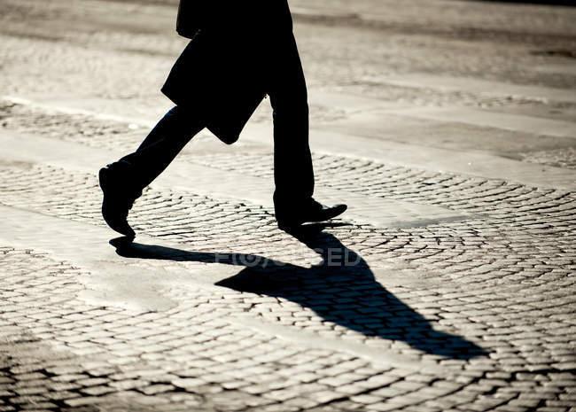 Pernas de pessoa andando sobre pedras de paralelepípedos — Fotografia de Stock