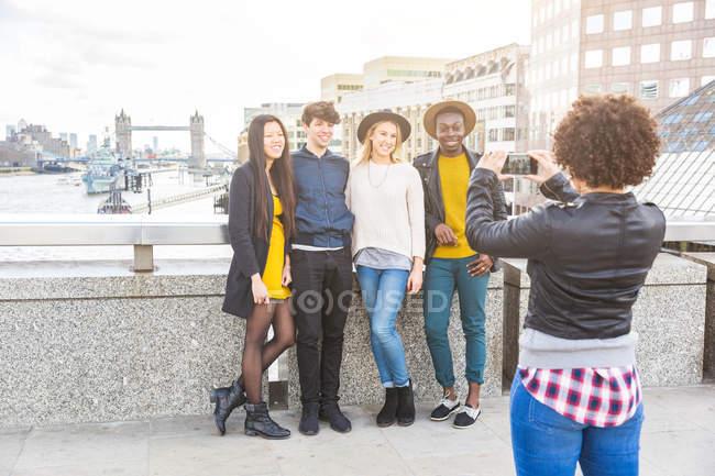 Frau auf Brücke im Stadtgebiet fotografiert Freunde mit Smartphone, London, Großbritannien — Stockfoto