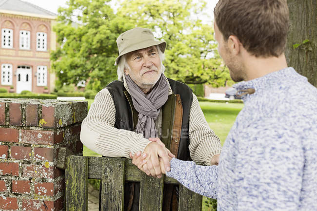 Senior man and mid adult man shaking hands over gate — Stock Photo