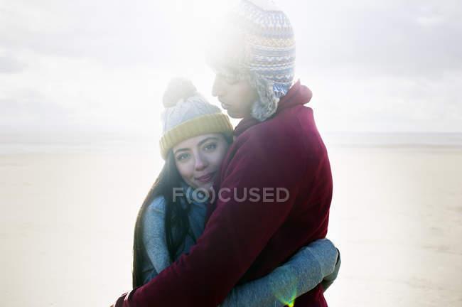 Молодая пара обнимается на пляже — стоковое фото