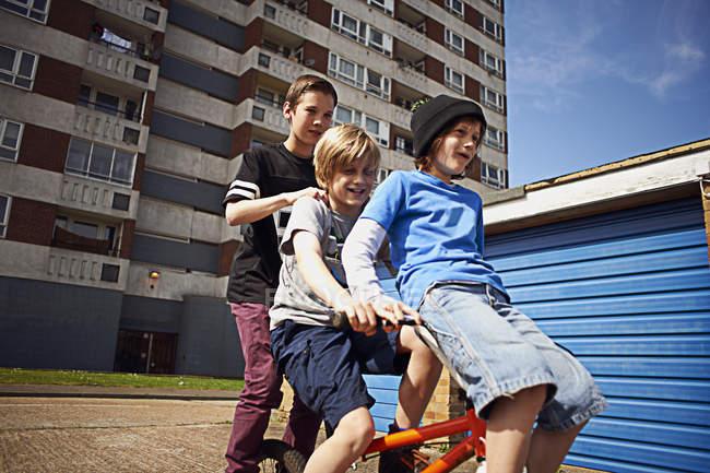 Boy giving male friends ride on bike in London, UK — Stock Photo