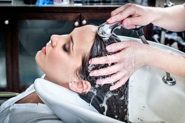 Жіночий перукар промивання молоді жінки клієнта волосся в салоні — стокове фото