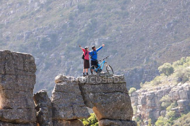 Couple VTT célébrant sur la formation rocheuse — Photo de stock