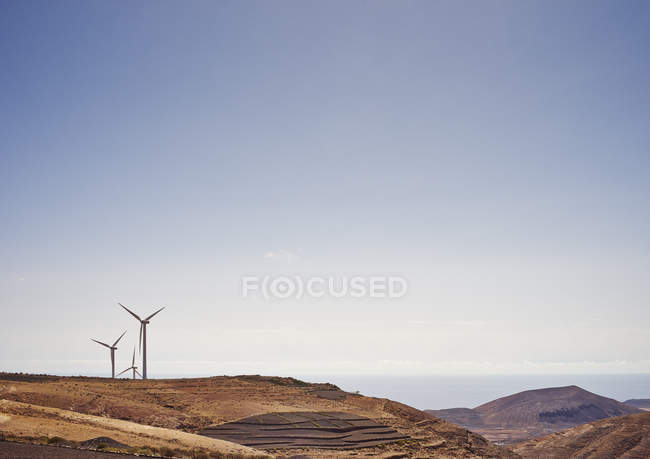 Wind turbines on hill with clear blue sky — Stock Photo