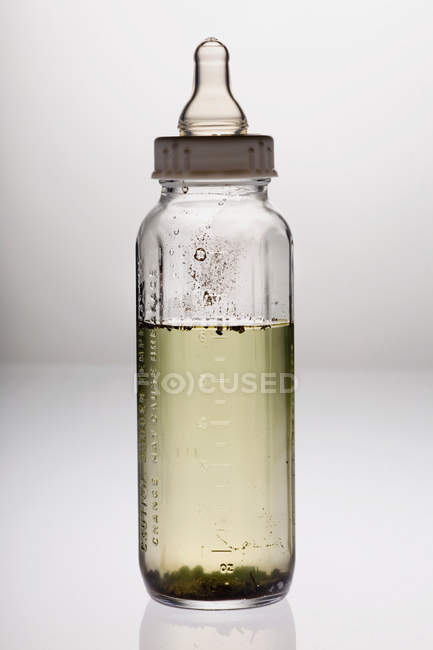 Baby bottle with dirty water placed on table, health concept — Stock Photo
