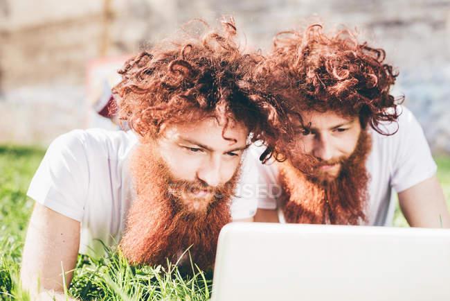 Junge männliche Hipster-Zwillinge mit roten Haaren und Bärten liegen im Park und stöbern im Laptop — Stockfoto