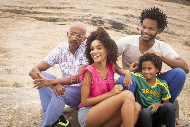 Grandfather and family sitting chatting on rock, Ipanema Beach, Rio De Janeiro, Brazil — Stock Photo