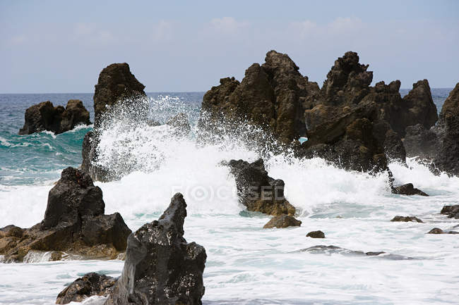 Black lava rock formations with breaking wave — Stock Photo