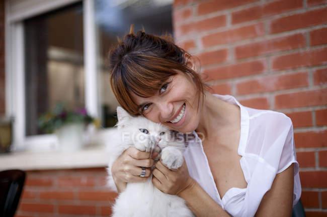 Портрет взрослой женщины и кошки на пороге — стоковое фото