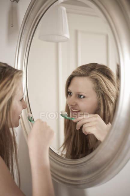 Teenage girl brushing teeth in bathroom by mirror — Stock Photo