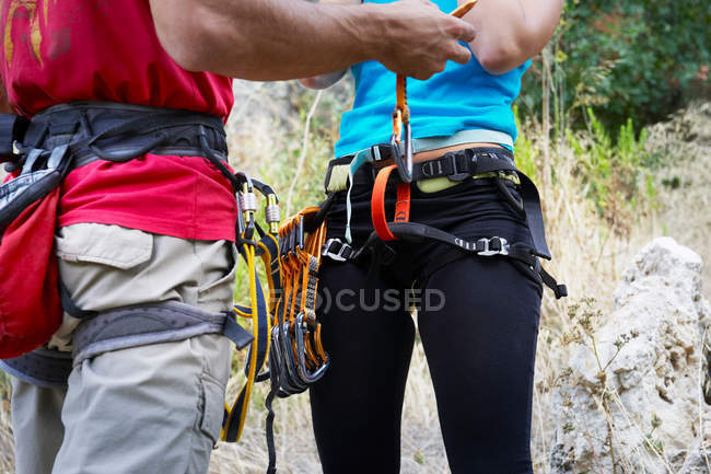 Cropped shot of male and female climbers with sport equipment — Stock Photo