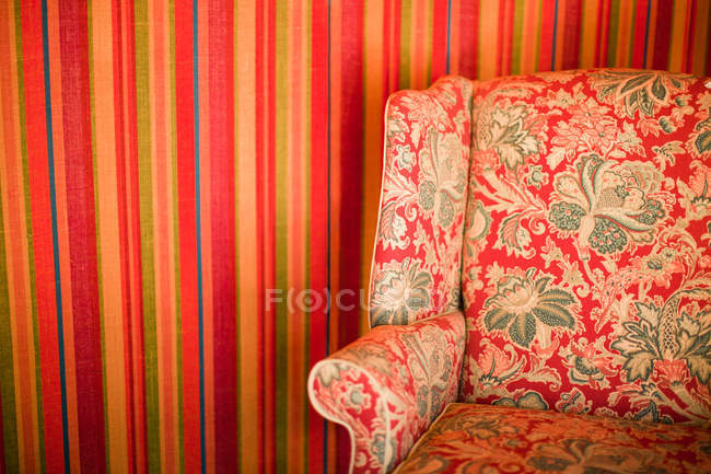 Floral patterned chair against striped wall — Stock Photo