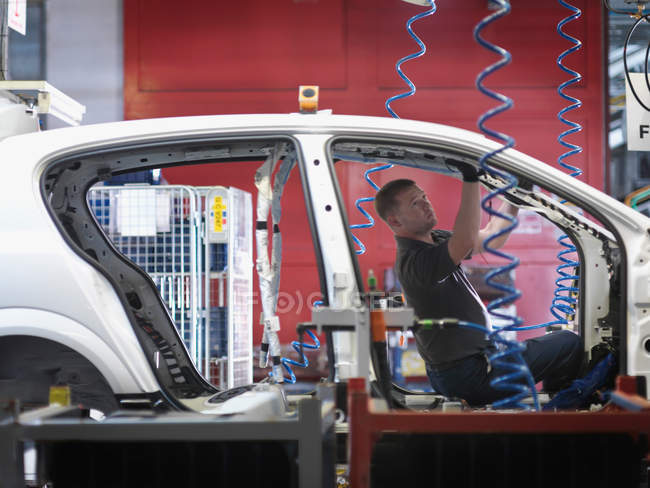 Worker Assembling Car On Production Line — Stock Photo