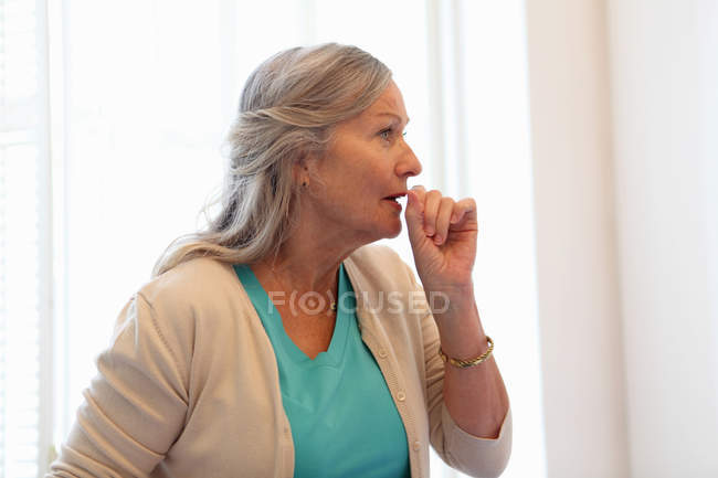 Older woman coughing into her hand — Stock Photo