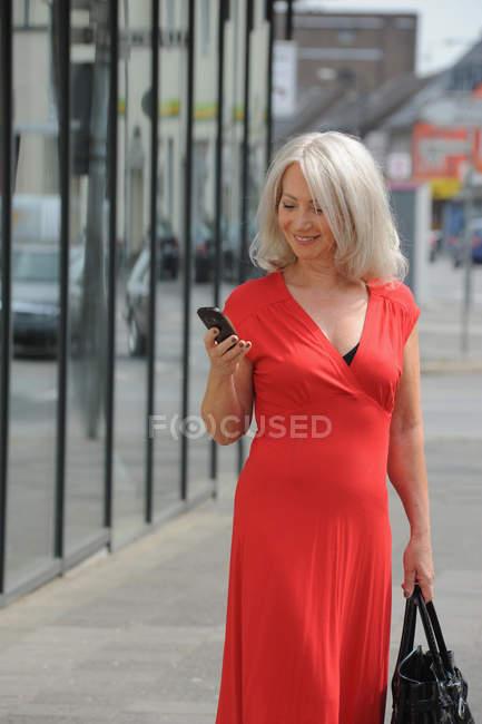Mujer mayor usando el teléfono celular al aire libre - foto de stock