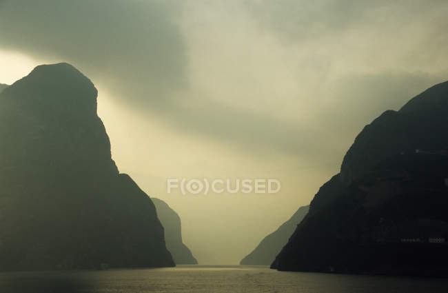 Scenic view of River gorge surrounded with mountains in foggy weather — Stock Photo