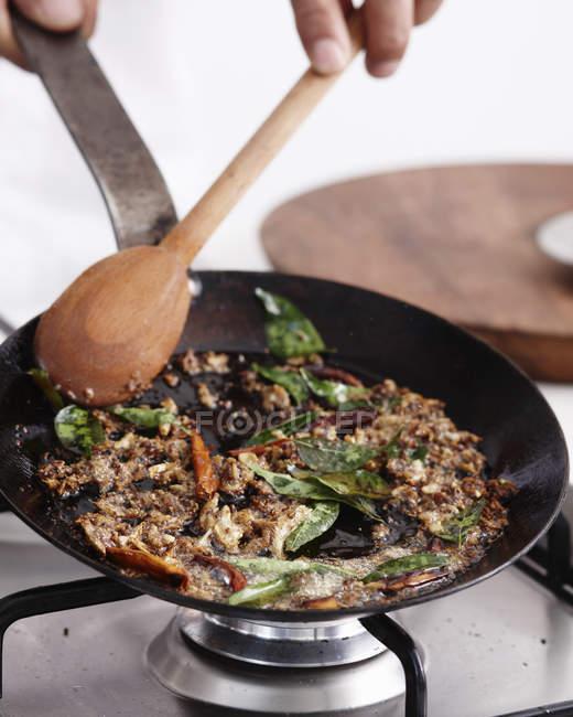 Close-up das mãos do cozinheiro chefe que fazem o prato do caril — Fotografia de Stock