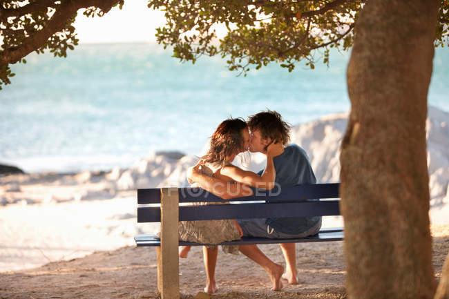 Пара цілуватися на лавці в парку — стокове фото
