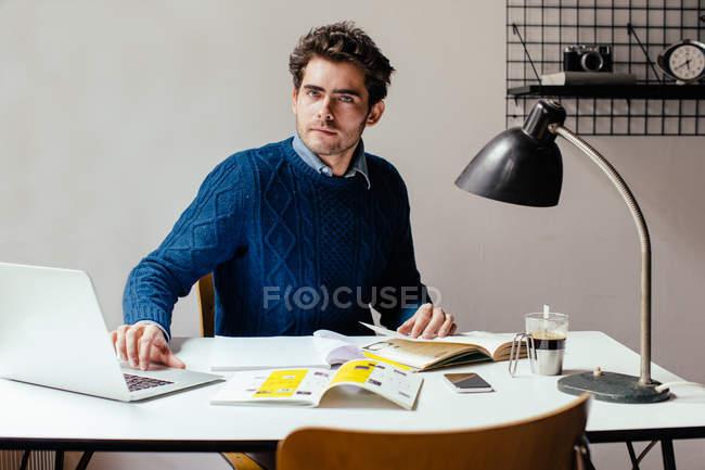 Jeune homme à l'aide d'ordinateur portable au bureau — Photo de stock