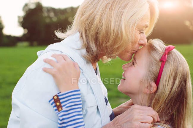 Grandmother kissing granddaughter on forehead — Stock Photo
