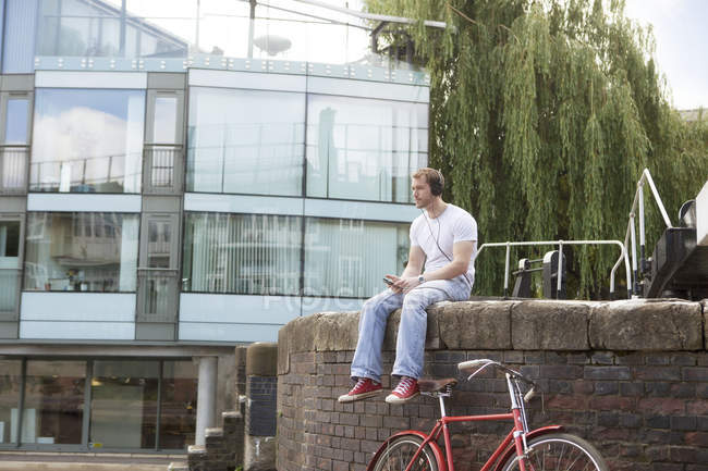 Man listening to music by canal, East London, UK — Stock Photo