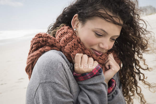 Portrait of young woman wrapped in scarf on windy beach, Western Cape, South Africa — Stock Photo