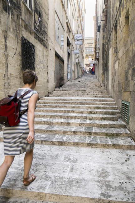 Female tourist walking up stairs, Valletta, Malta — Stock Photo