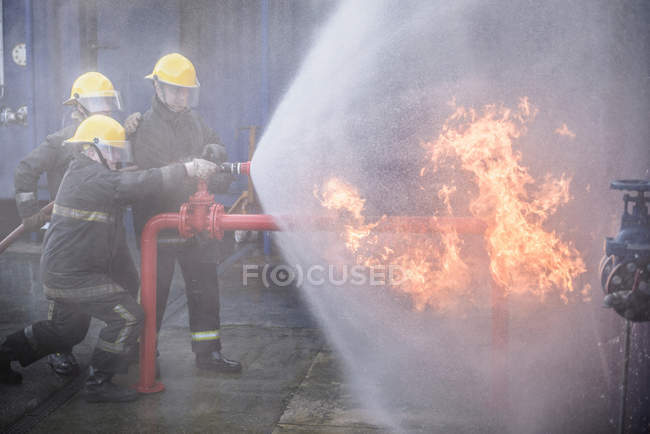 Three firefighters putting out fire in fire simulation training facility — Stock Photo