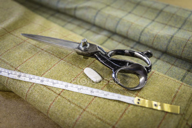 Harris tweed material and scissors in clothing factory — Stock Photo