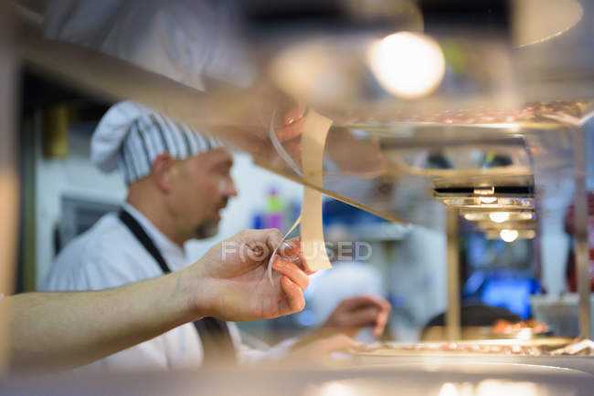 Chef checking order in traditional Italian restaurant kitchen — Stock Photo
